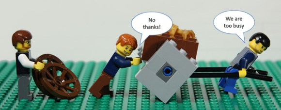 "two lego men push a lego cart with square wheels while a lego man behind them holds a circular wheel. The two men reply ""no thanks"" and ""too busy"" and the title reads ""are you too busy to improve"""
